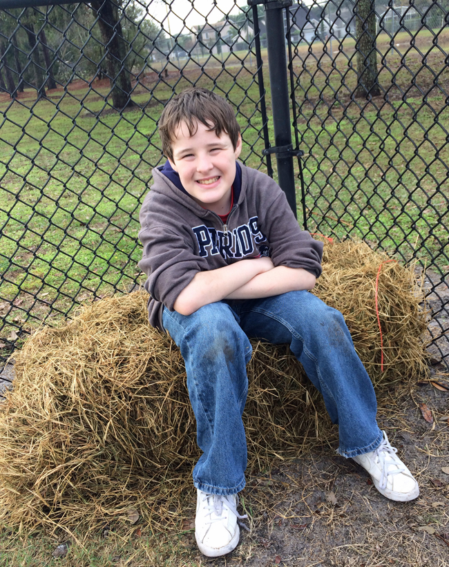 They spread out hay in the dog park to dry up the wet, muddy areas. Mikey's sitting on a bale of hay they left in the corner of the park.