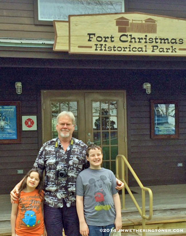 Granddad with Mikey and Heather in front of the Fort Christmas park entrance.