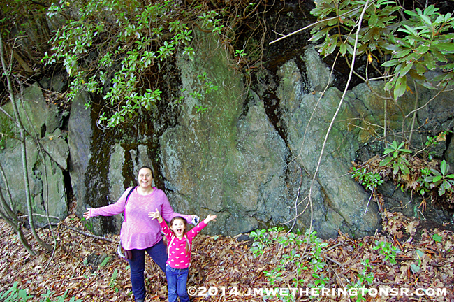 Amber and Abby pose in front of a huge rock wall on the side of the mountain as we continue up to the lake.