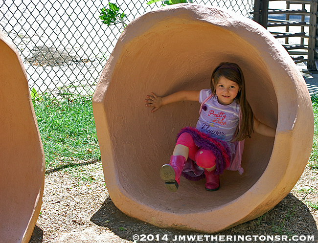 Over at the Farm, near the chicken coop, Abby pretends to be a chick breaking out of a giant egg shell.