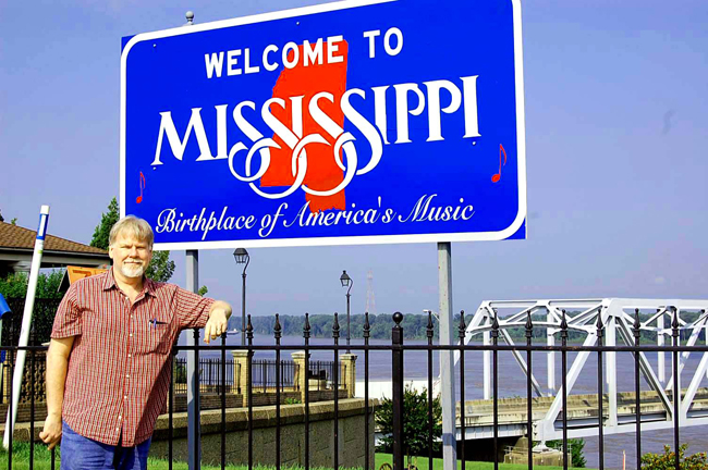 Me in Vicksburg, MS in front of a welcome to Mississippi sign on the Mississippi River.