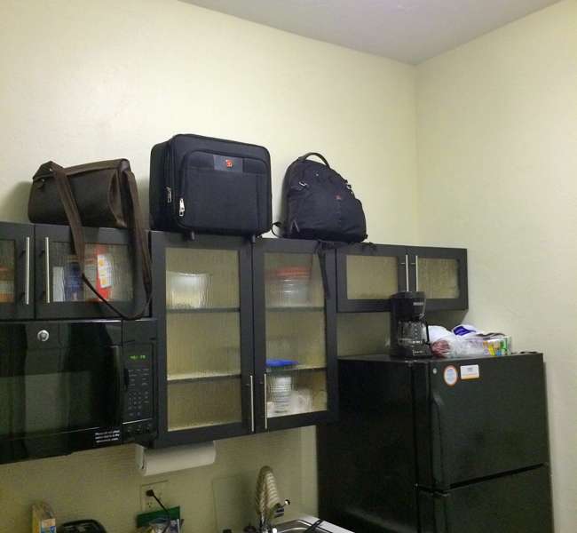 Luggage on top of Kitchen Cabinets