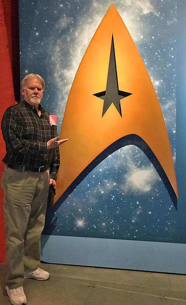 Me standing next to large Starfleet emblem at Museum of Pop Culture