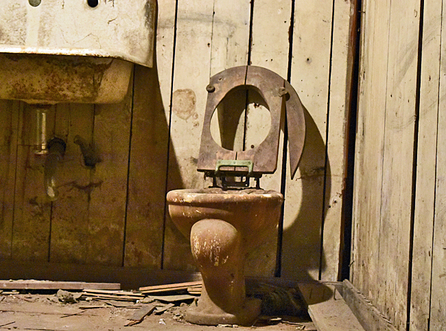 Bathroom with old, wodden toilet seat in Underground Seattle.